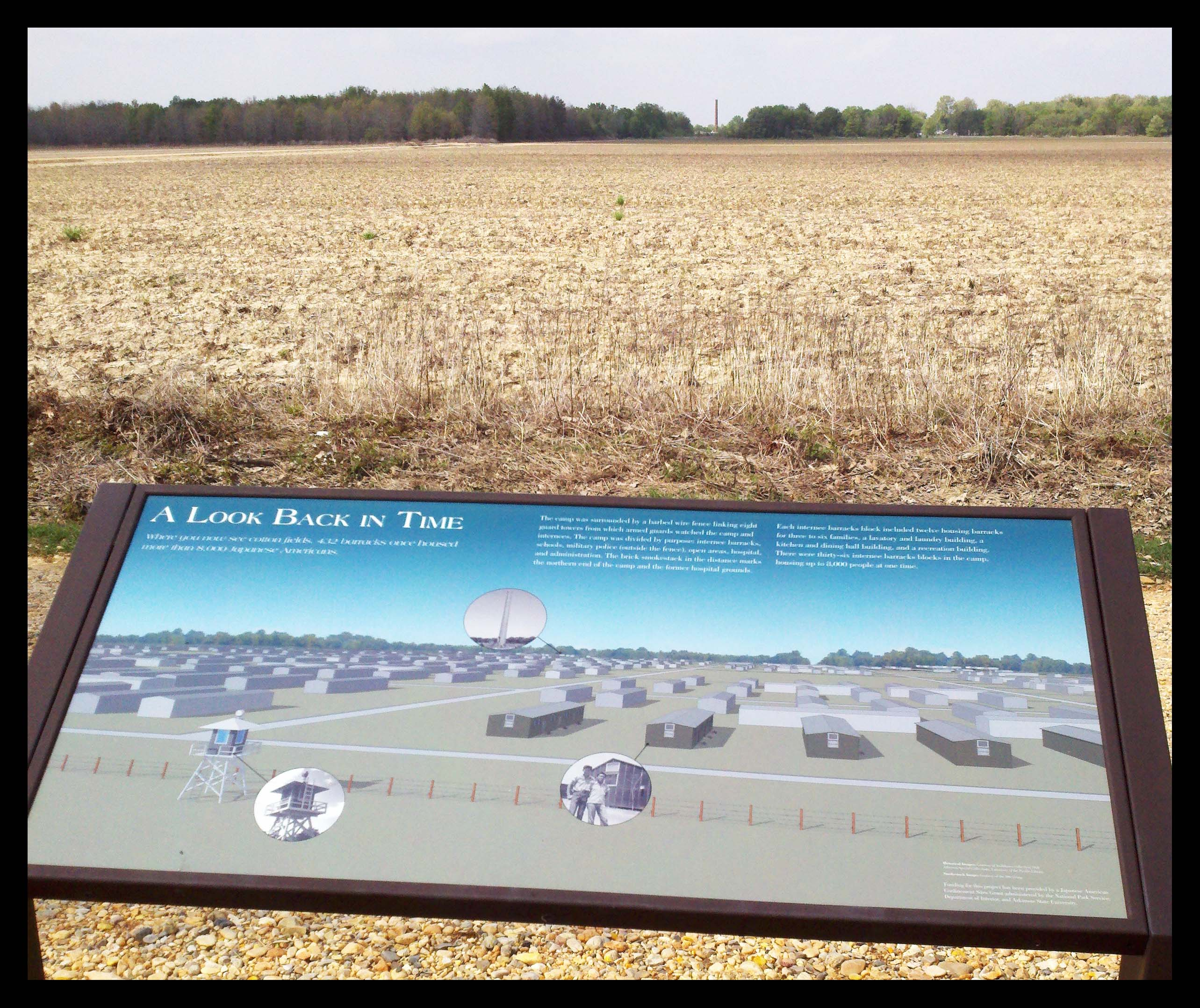 Interpretive panel with hospital smokestack in the distance.